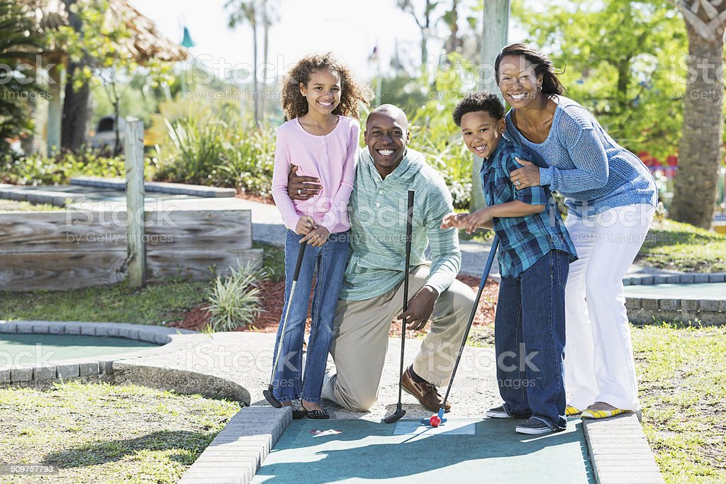 Family playing miniature golf stock photo