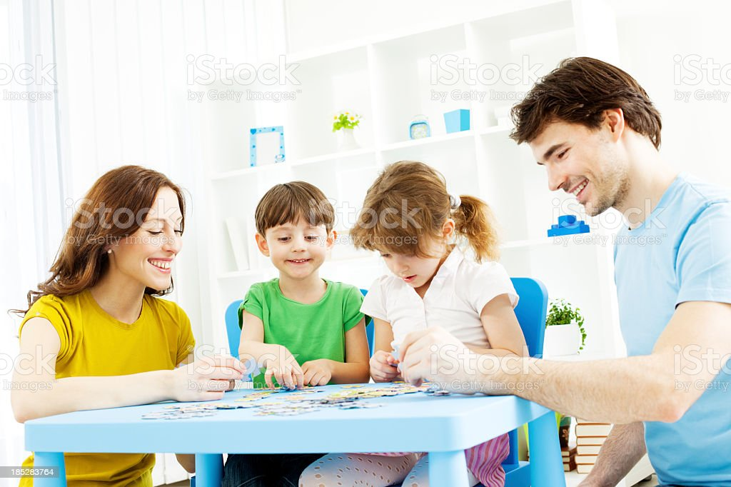 Family Playing Puzzle Game at home. royalty-free stock photo