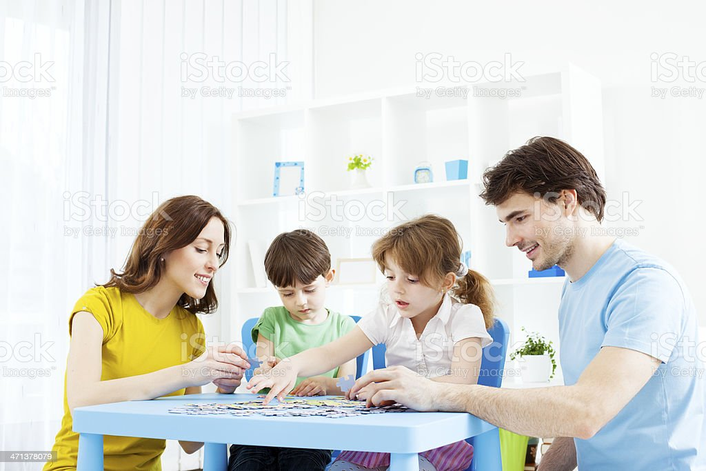 Family Playing Puzzle Game at home. stock photo