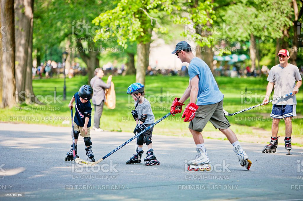 Family playing roller hockey in Central Park, New York stock photo
