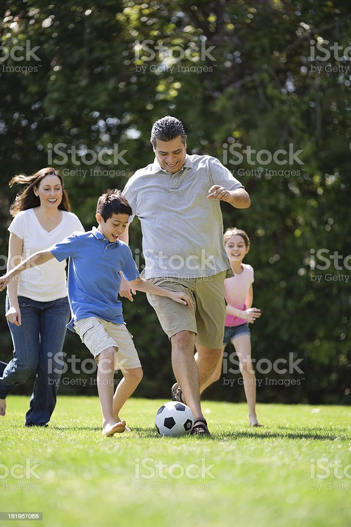 Family Playing Soccer In Park royalty-free stock photo
