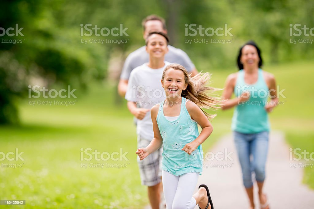 Family Playing Tag in the Park stock photo