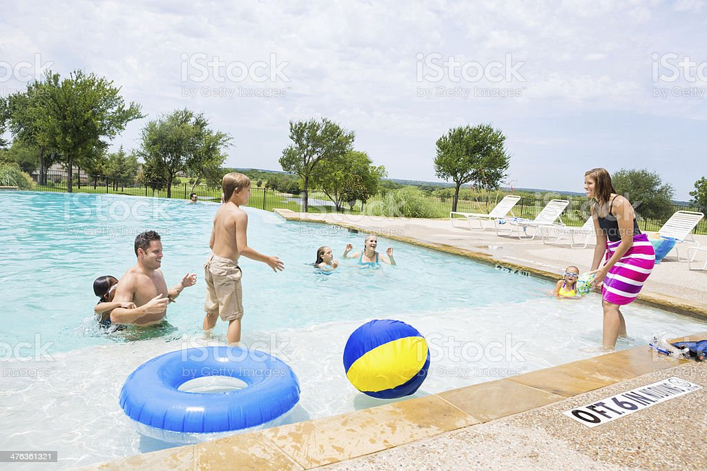 Family playing together in community swimming pool royalty-free stock photo