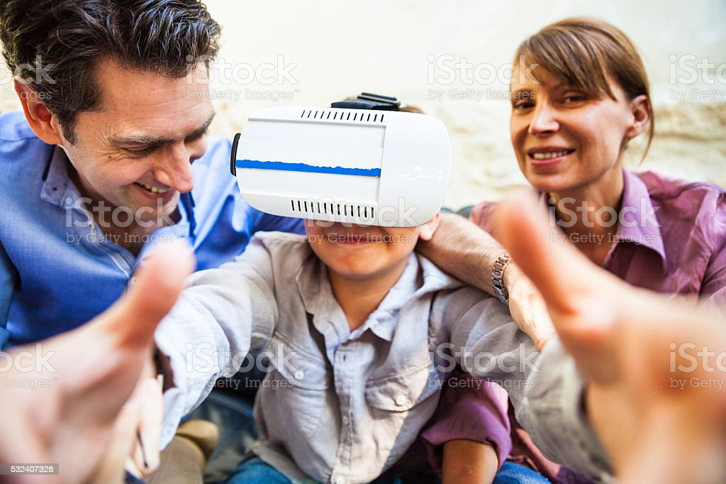 Family playing together with a VR headset on the coach stock photo