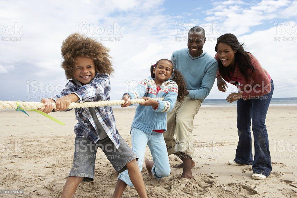 Family playing tug of war on beach stock photo