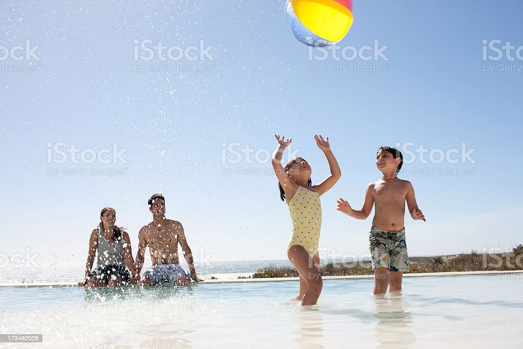 Family playing with ball in swimming pool royalty-free stock photo