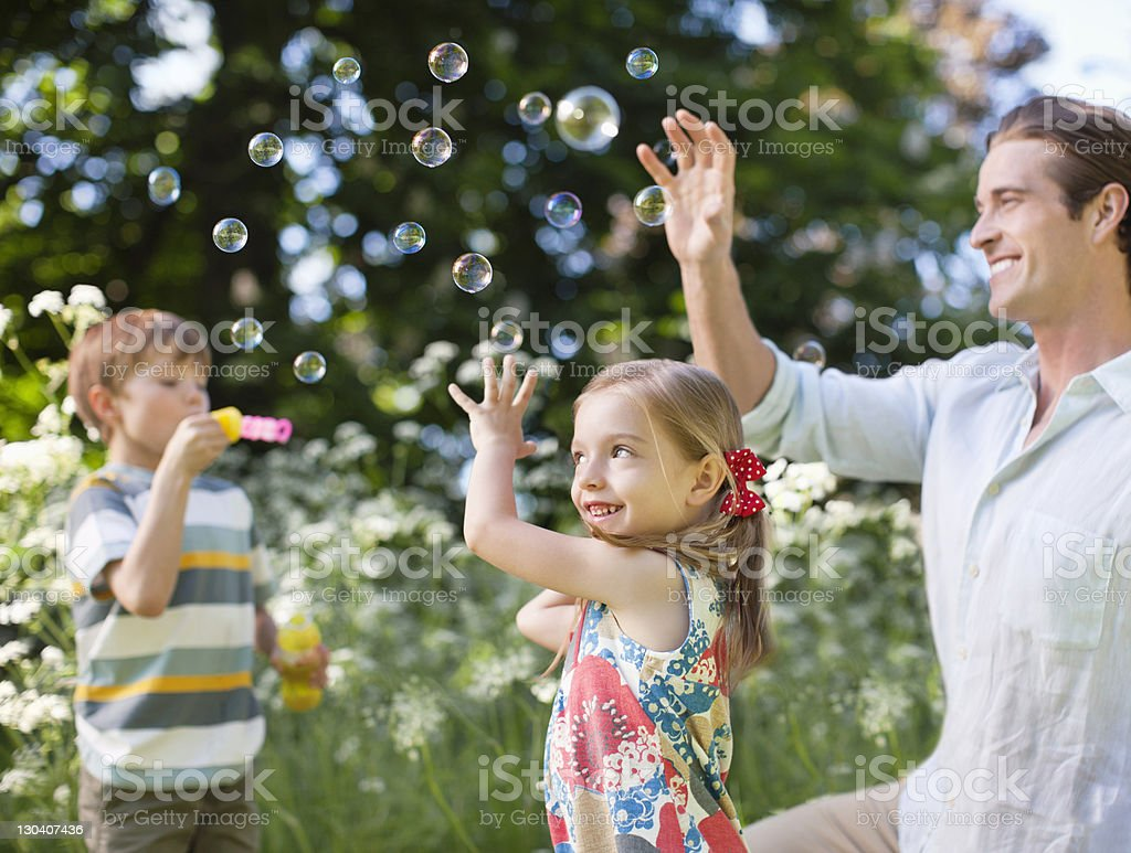 Family playing with bubbles in park royalty-free stock photo