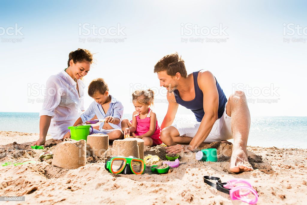 Family playing with sand in summer. stock photo