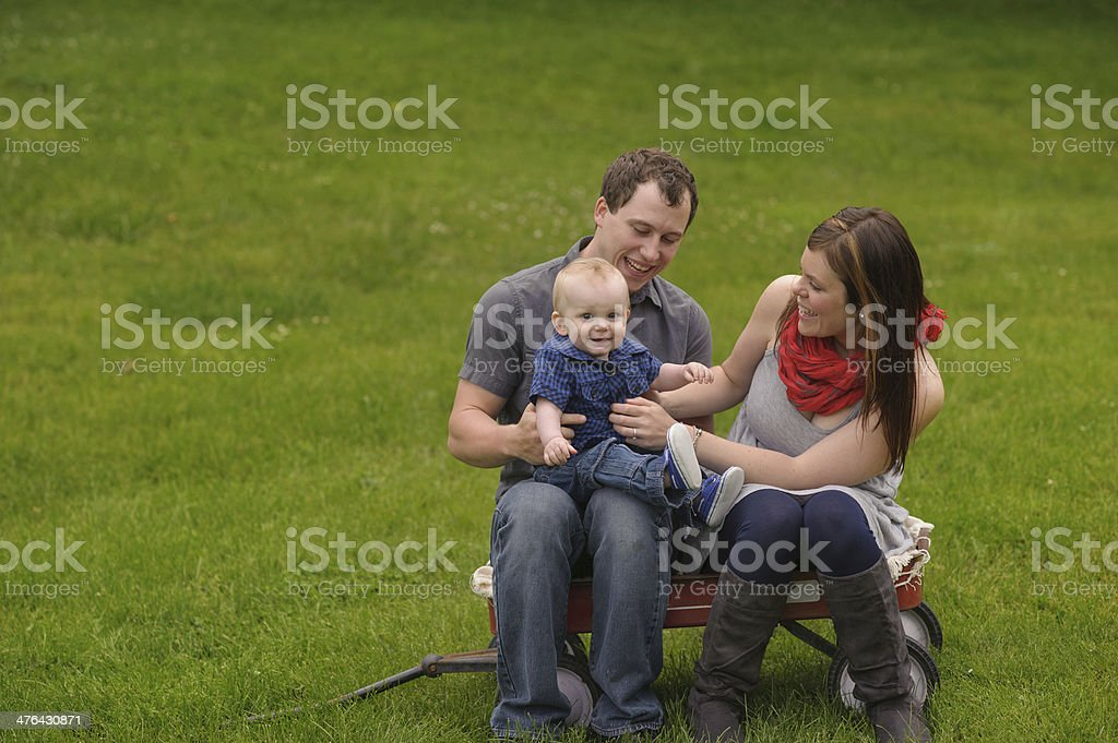 Family Playing with Son While Sitting on Wagon Outside royalty-free stock photo