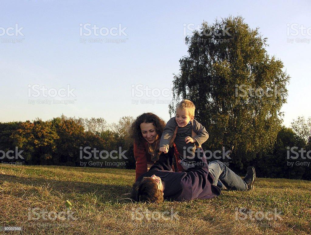 family plays autumn sundown on glade royalty-free stock photo