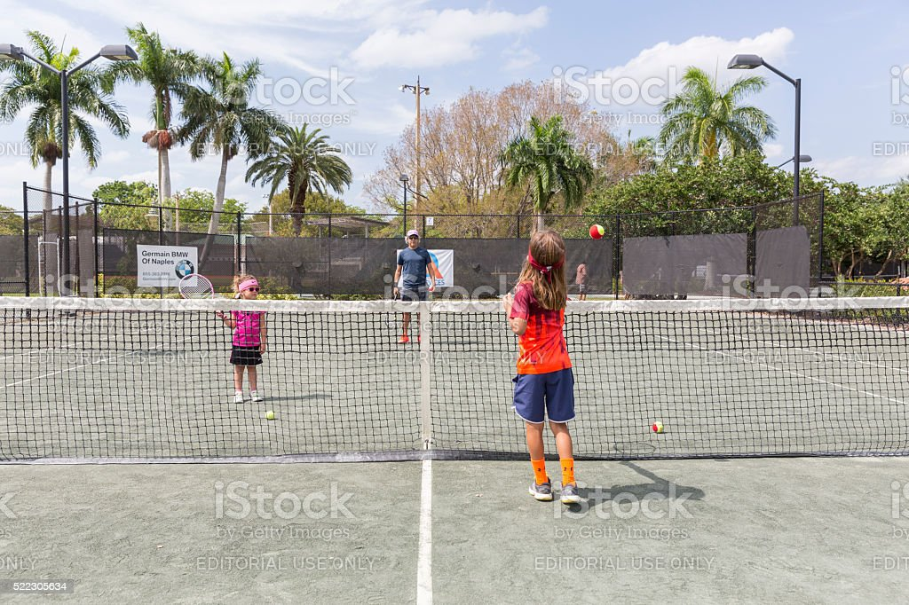 Family Plays Tennis Together on a Sunday stock photo