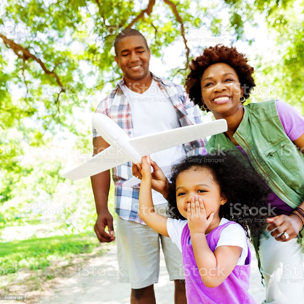 Family plays with toy airplane in the park stock photo
