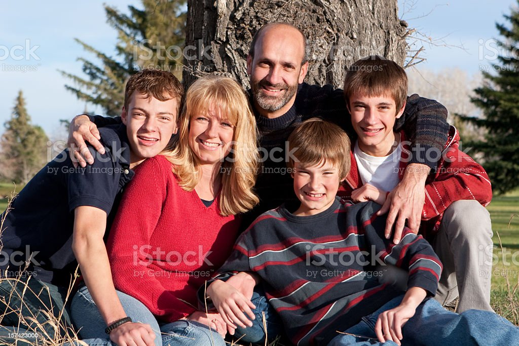 Family portrait in front of a tree in the park royalty-free stock photo