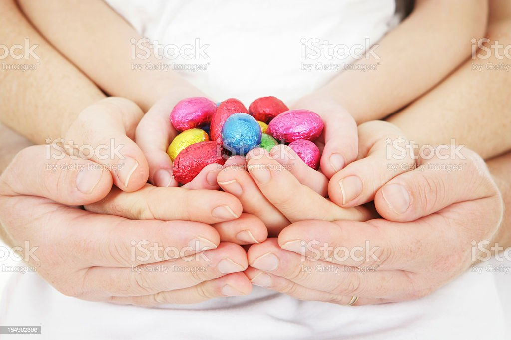 A family portrait of all their hands holding Easter eggs stock photo