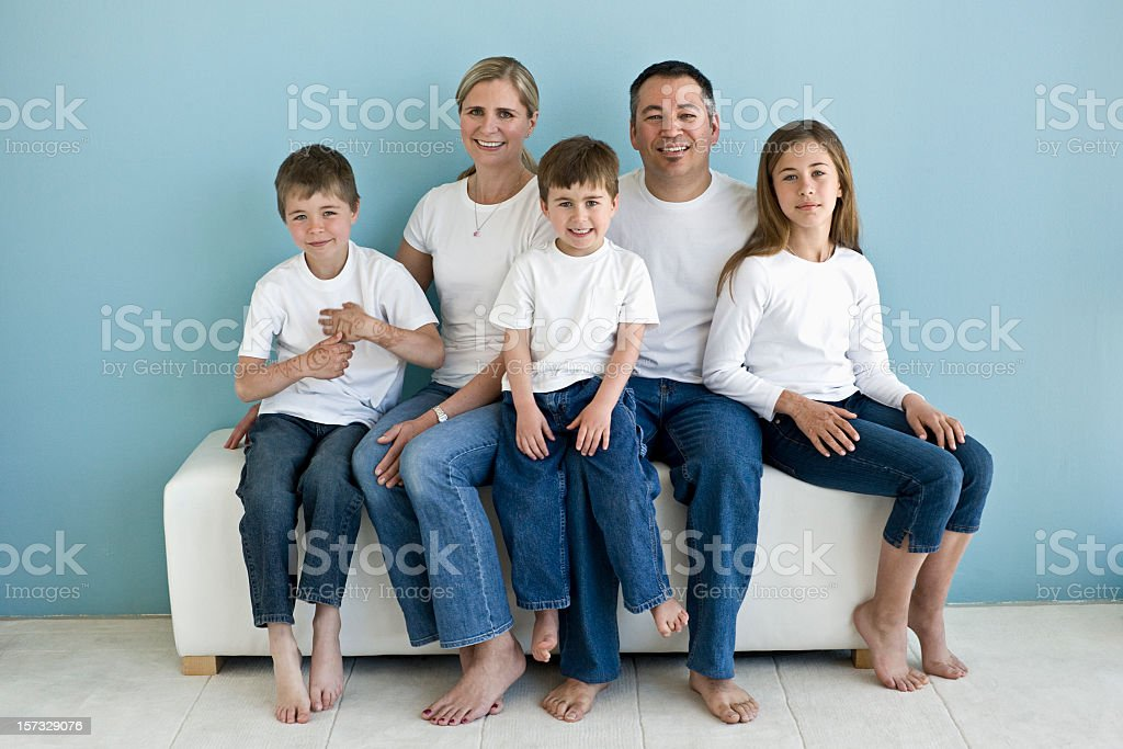 A family portrait of five in white T-shirts and blue jeans stock photo