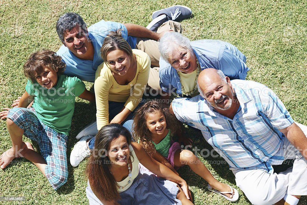 Family portrait of three generations relaxing on grass royalty-free stock photo