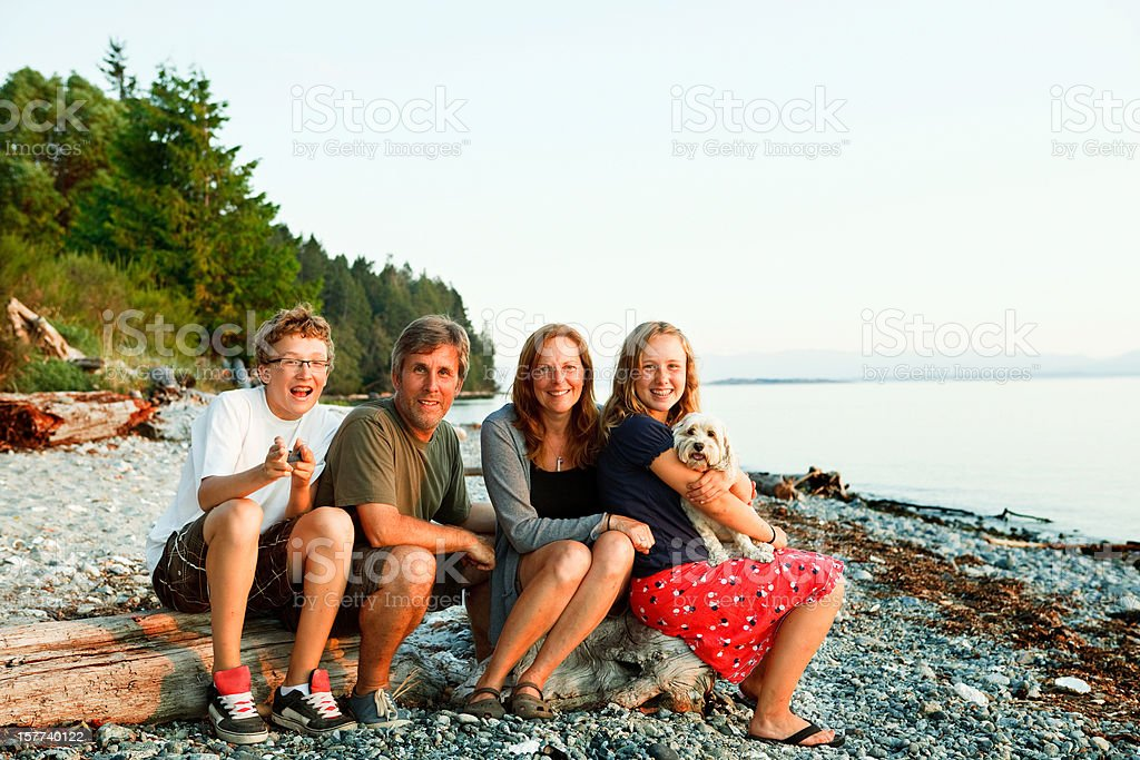 Family portrait sitting on a stoney beach. royalty-free stock photo