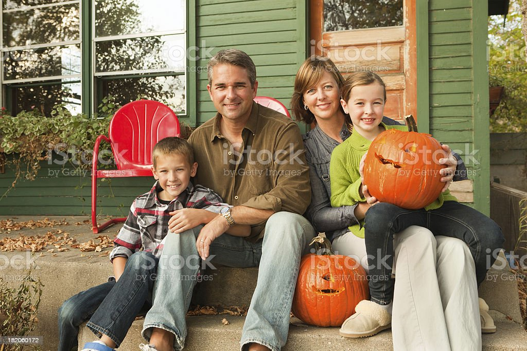 Family Portrait with Halloween Pumpkins in Front of House royalty-free stock photo