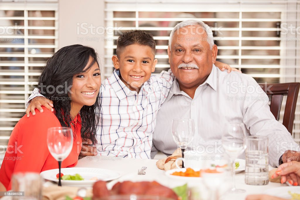 Family posing with grandfather for holiday photo. Dinner table. stock photo