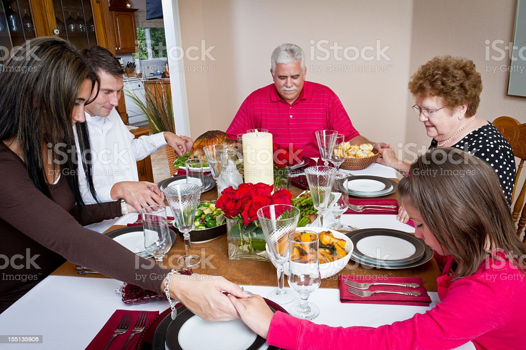 Family Praying at Thanksgiving or Christmas Dinner royalty-free stock photo
