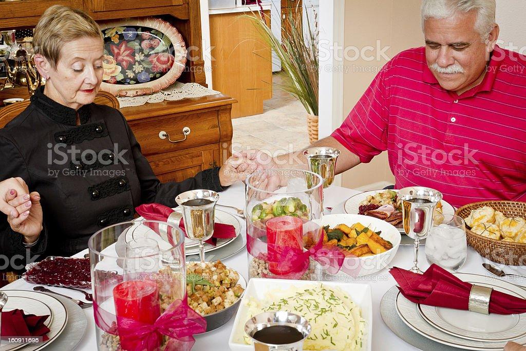 Family Praying at Thanksgiving or Christmas Dinner royalty-free stock photo
