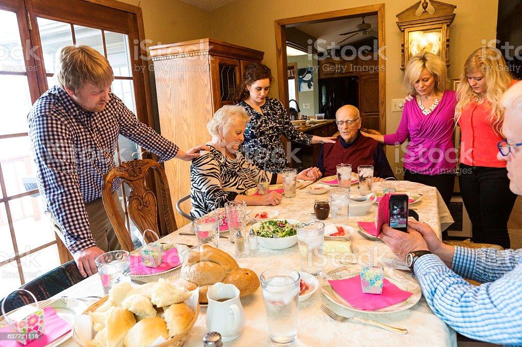 Family praying before dinner stock photo