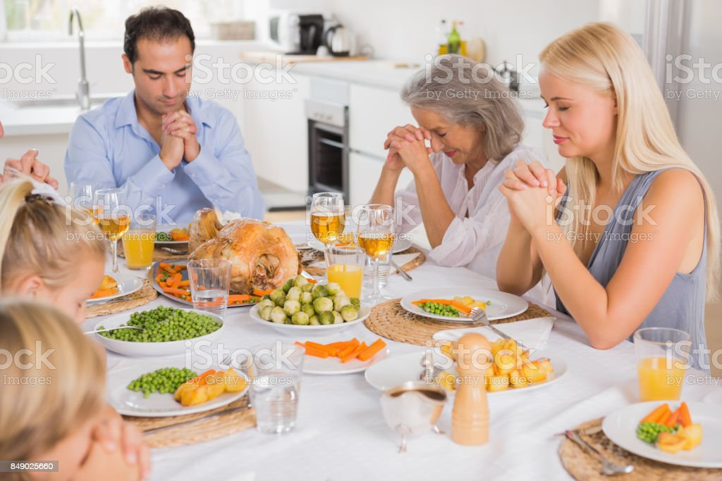 Family praying before dinner stock photo