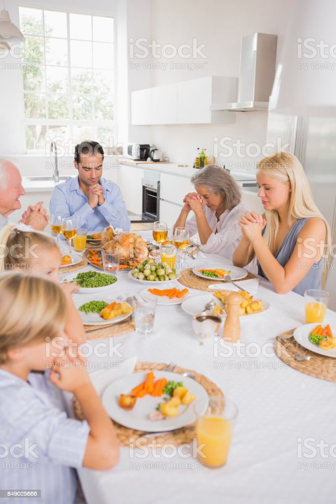 Family praying before eating stock photo