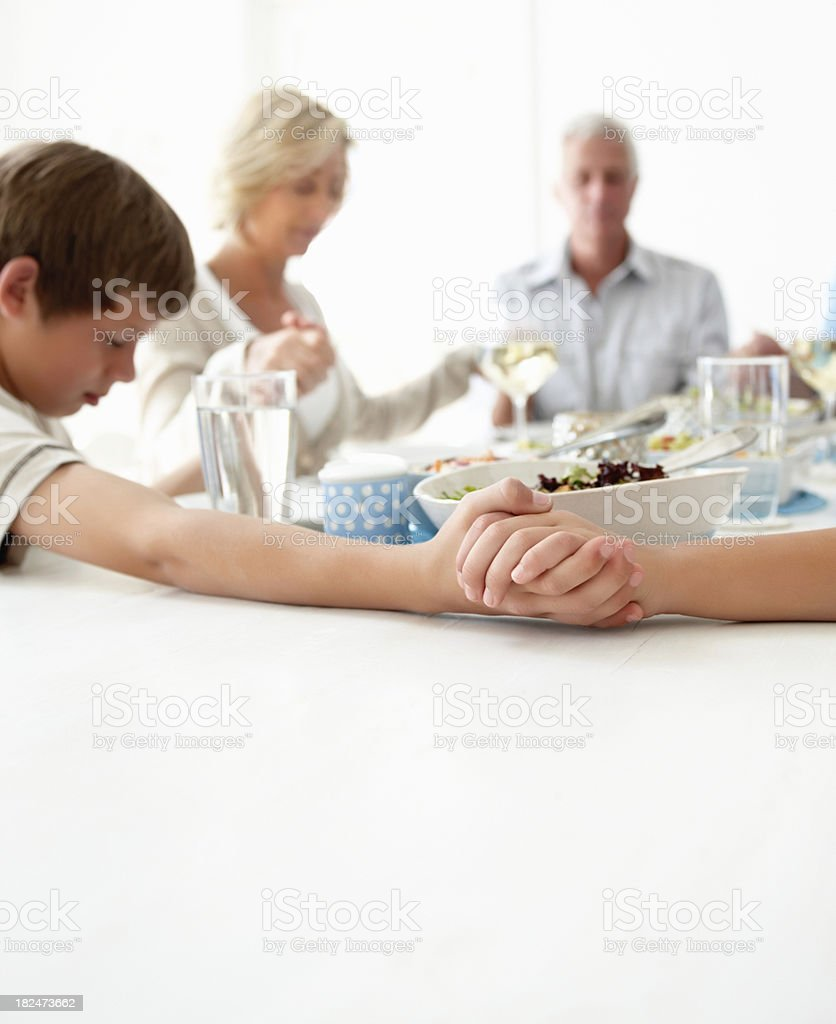 Family praying before having lunch stock photo