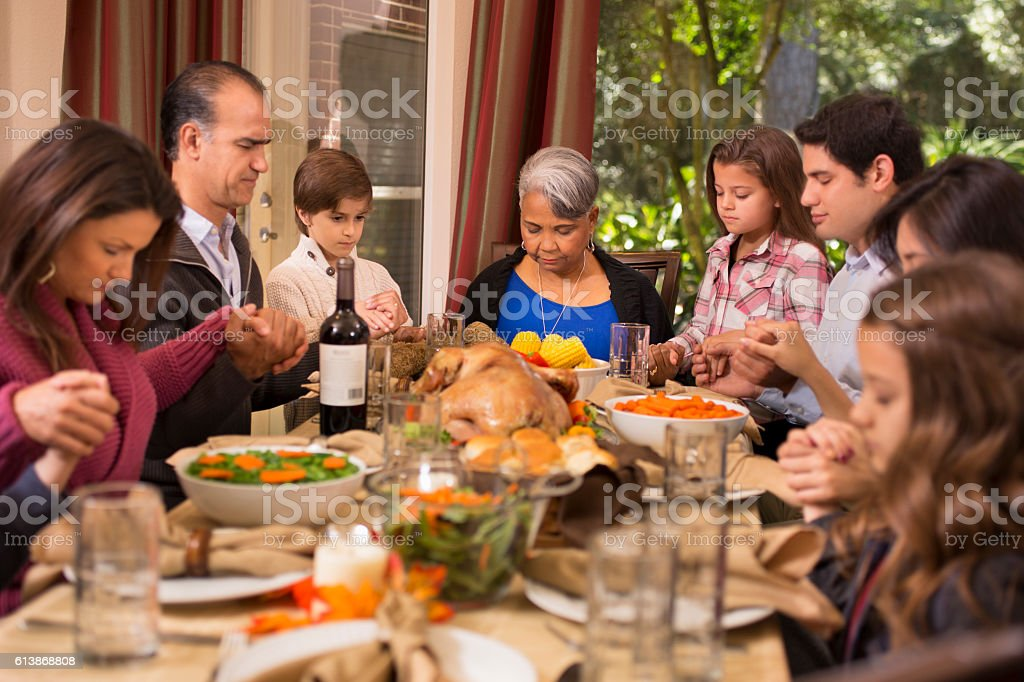 Family praying before Thanksgiving dinner at grandmother's home. stock photo