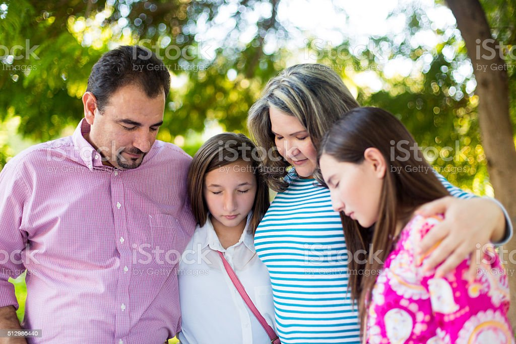 Family praying in a park stock photo