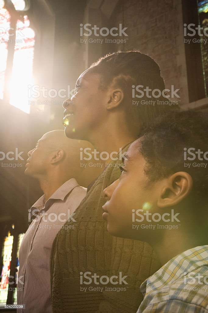 Family Praying in Church With Sunlight From Window stock photo