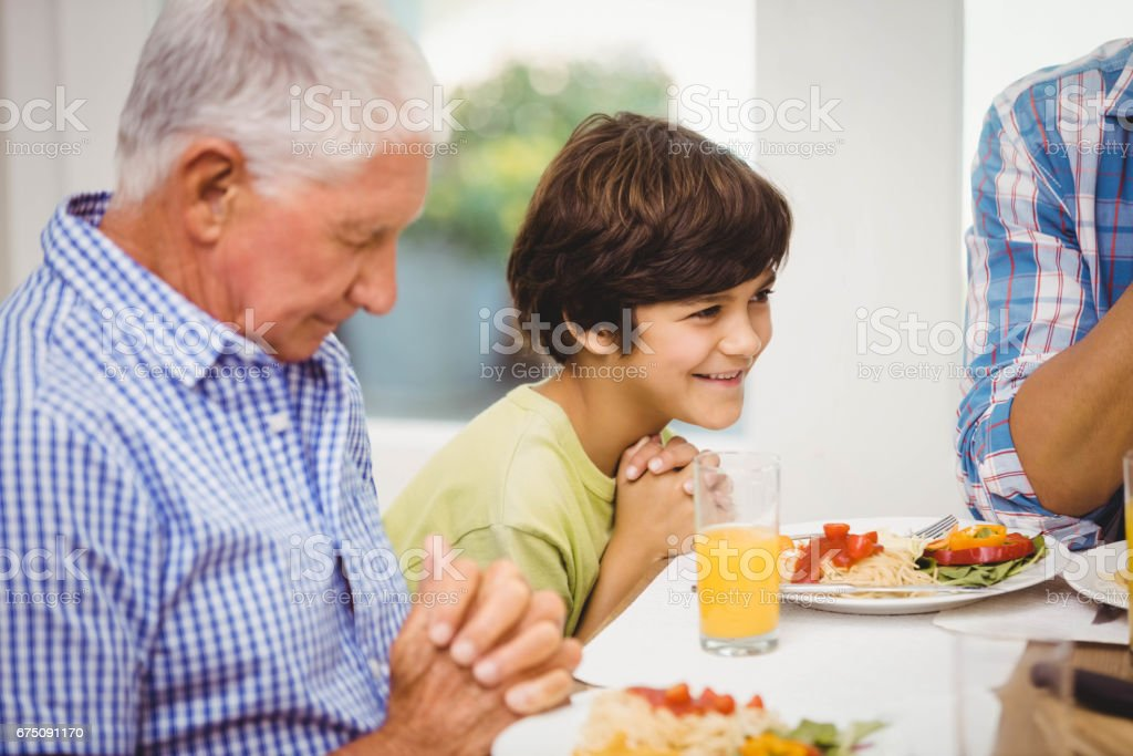 Family praying together before meal stock photo