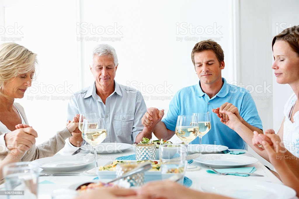 Family praying together before their meal stock photo
