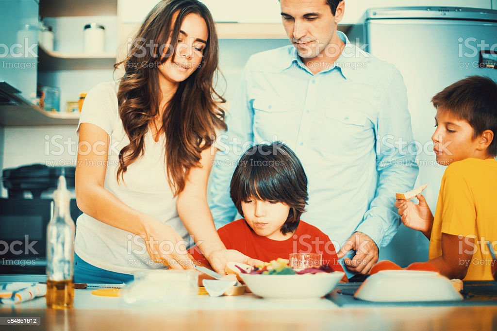 Family preparing  food in a kitchen. stock photo