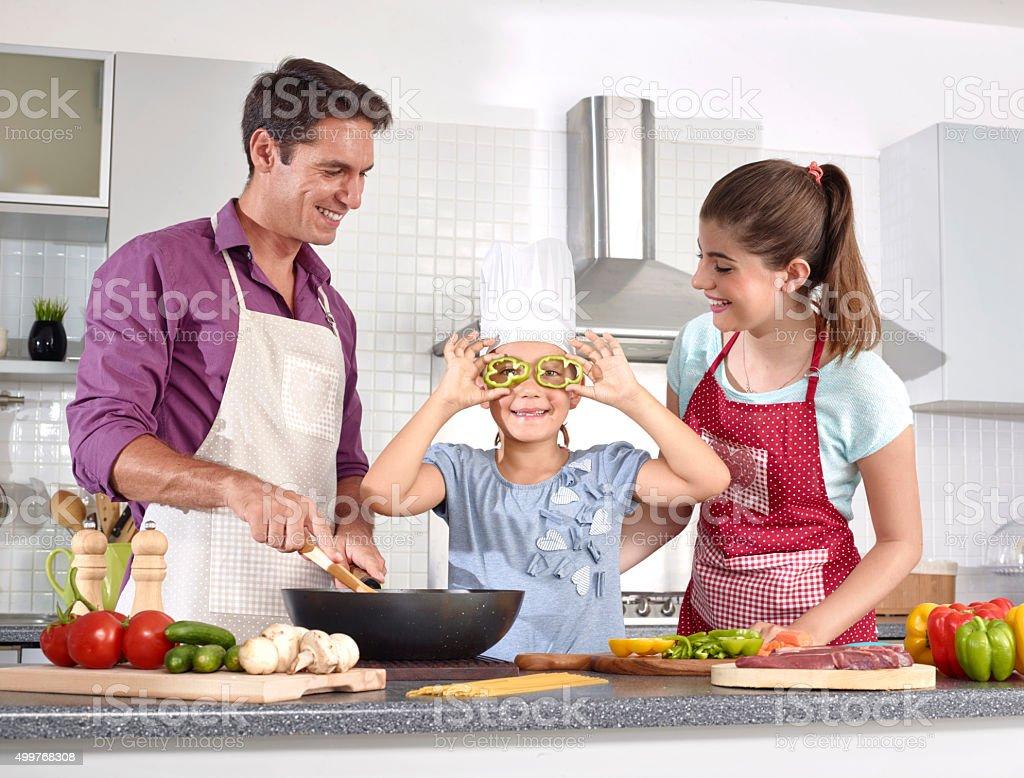 Family preparing food in kitchen stock photo