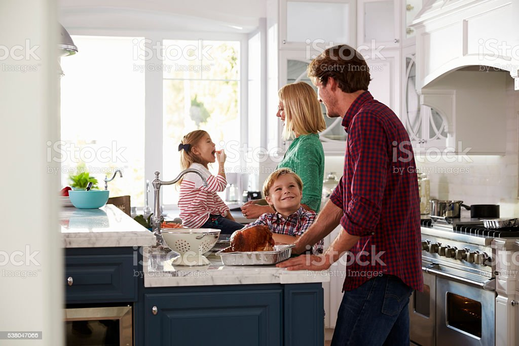 Family Preparing Roast Turkey Meal In Kitchen Together stock photo