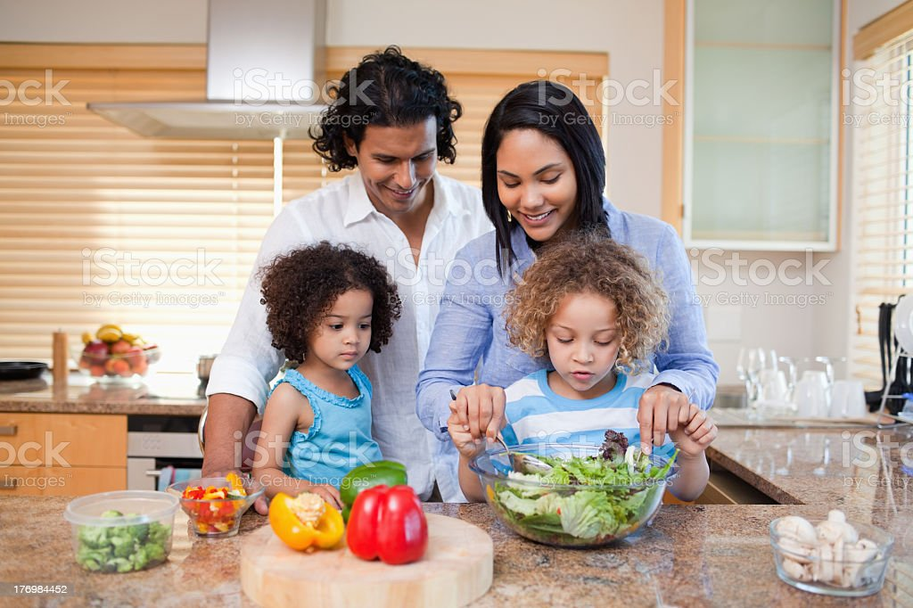 Family preparing salad together in the kitchen stock photo