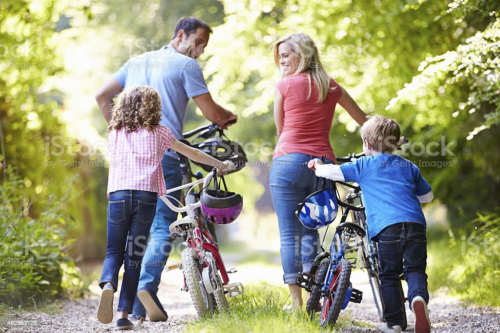 Family Pushing Bikes Along Country Track stock photo