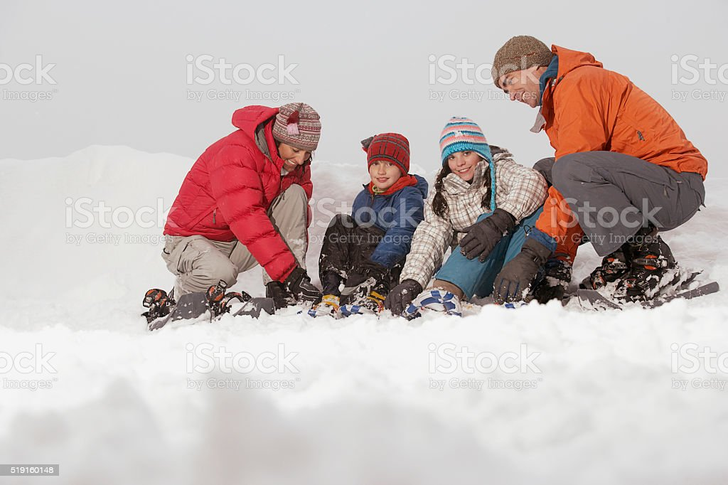 Family putting on snow shoes stock photo