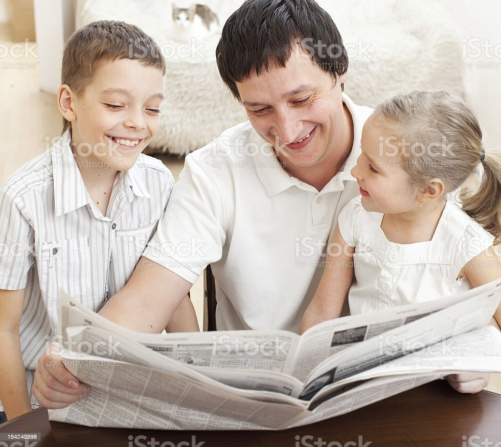 Family reading a newspaper royalty-free stock photo
