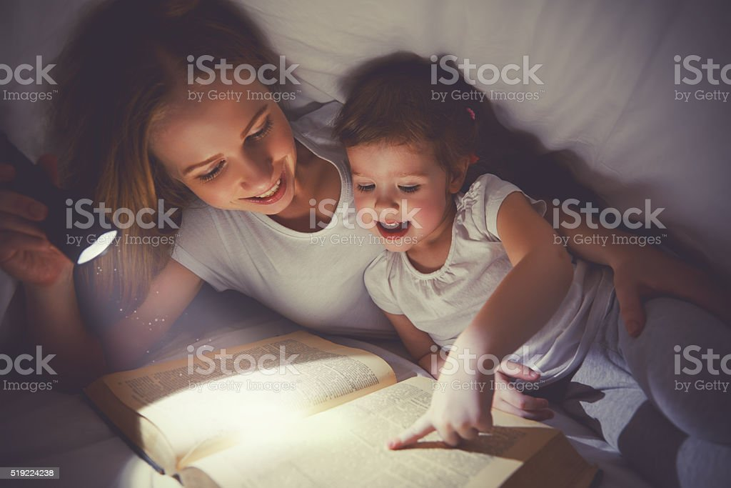 Family reading bedtime. Mom and child reading book stock photo