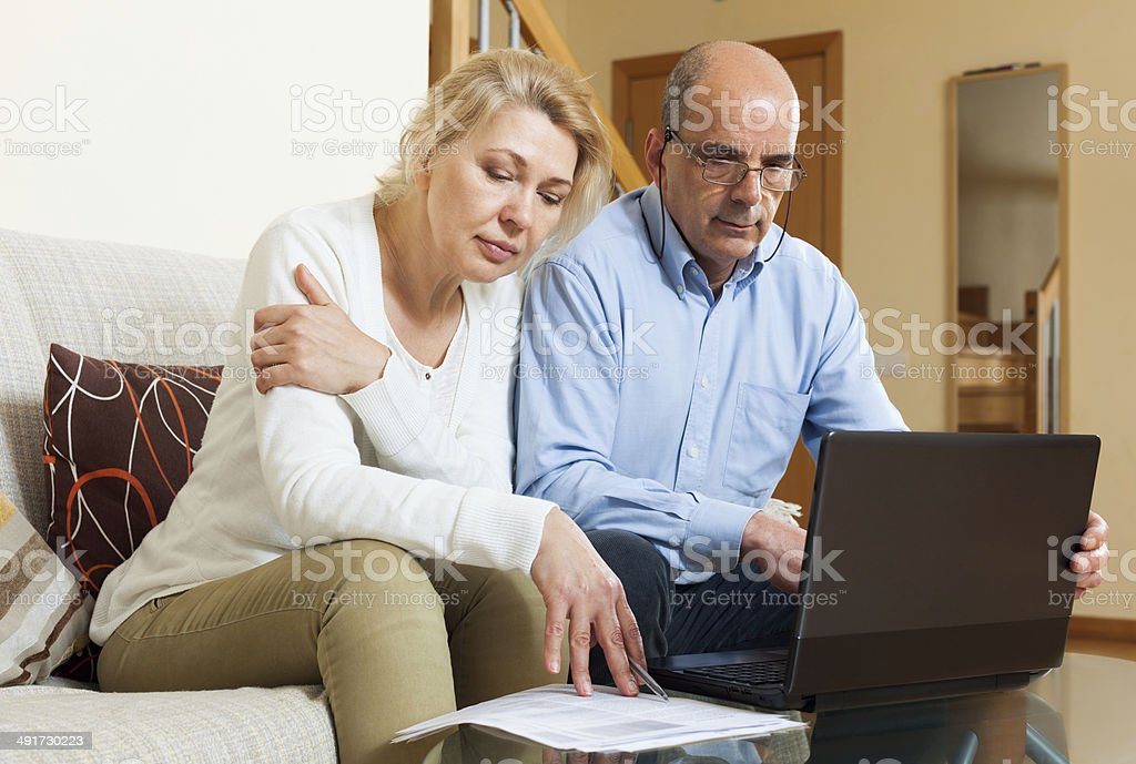 Family reading finance documents together and using laptop stock photo