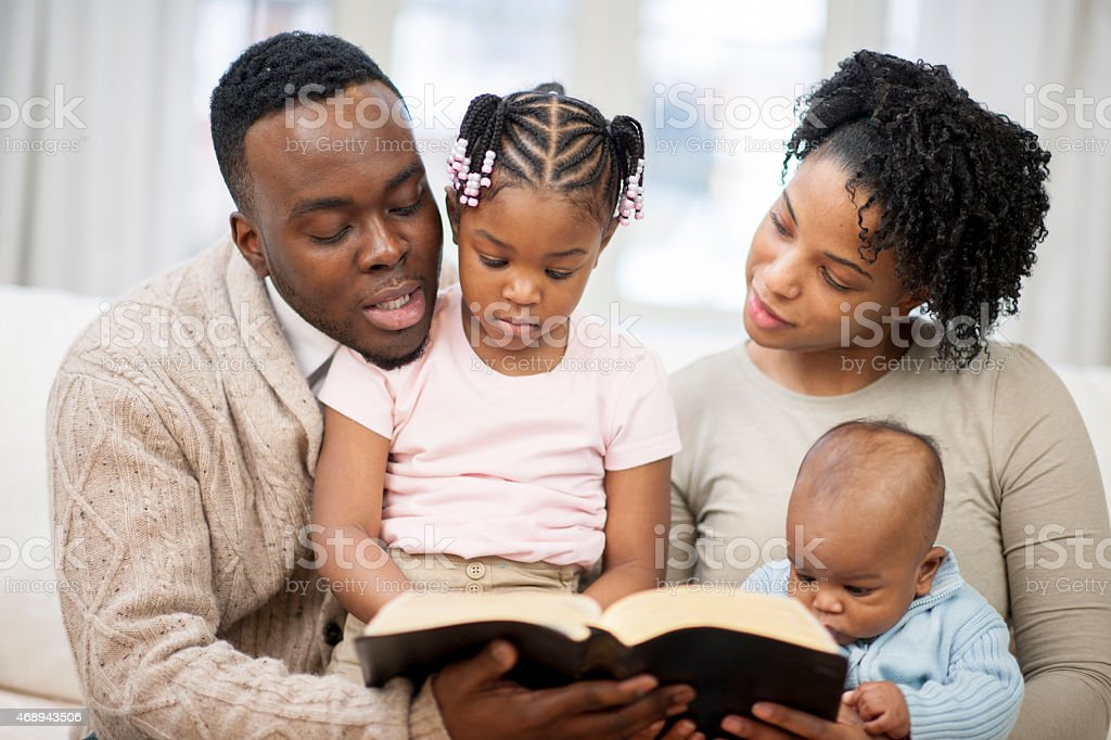 Family Reading the Bible Together stock photo