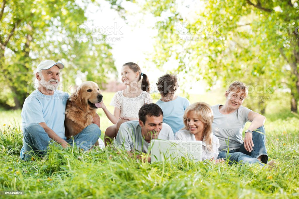 Family relaxing and looking at laptop in the park. royalty-free stock photo
