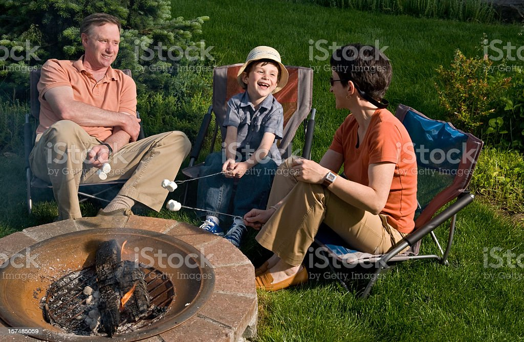 Family relaxing around fire pit stock photo