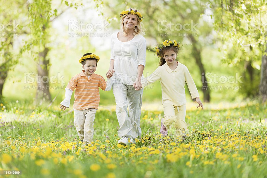 Family relaxing in park with flower wreaths on the heads. royalty-free stock photo