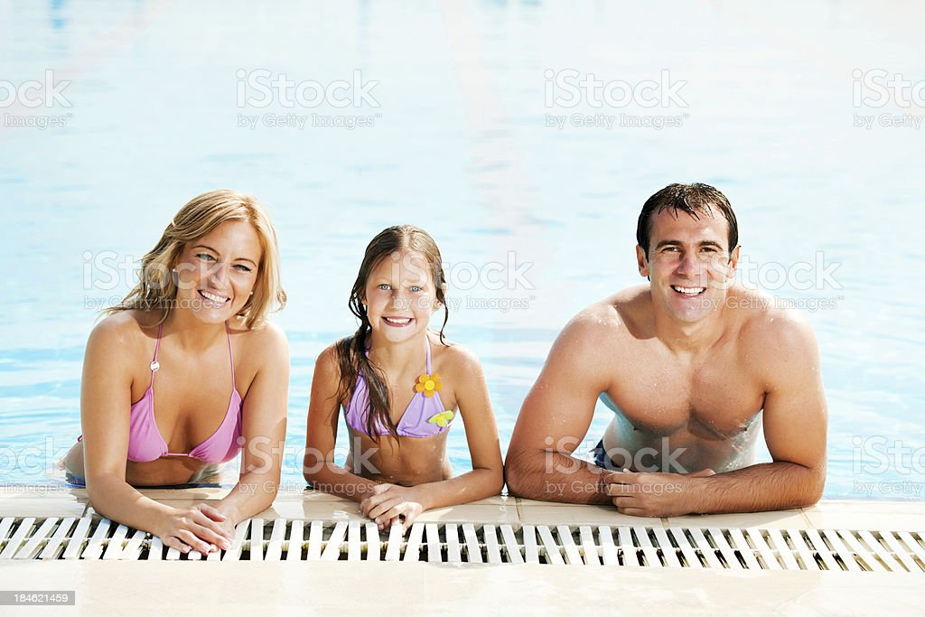 Family relaxing in swimming pool together. royalty-free stock photo