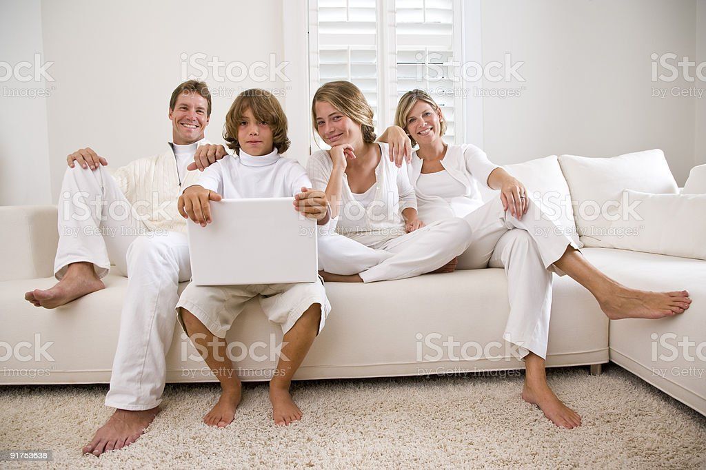 Family relaxing on sofa with laptop stock photo