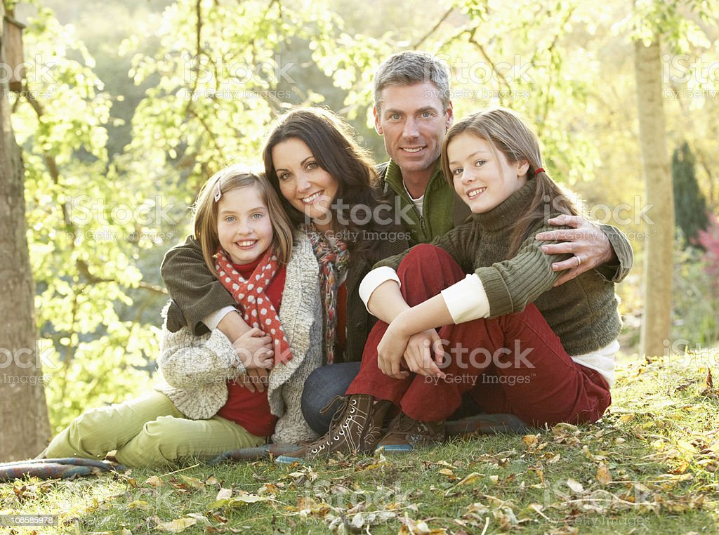 Family Relaxing Outdoors In Autumn Landscape